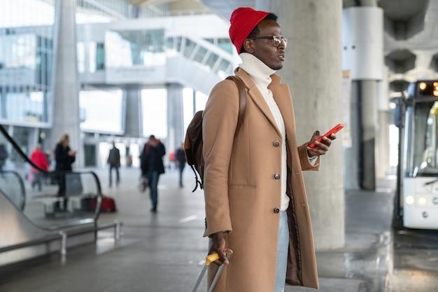 Afroamerikaanse reiziger duizendjarige man met koffer met mobiel