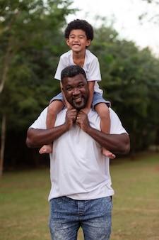 Afrojongen met zijn vader in het park op zijn nek