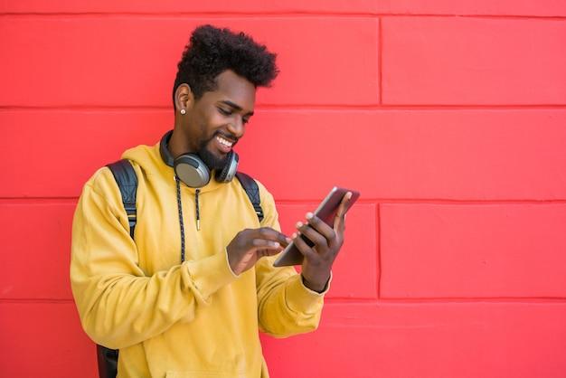 Afromens die zijn digitale tablet met oortelefoons gebruiken.