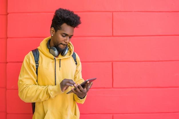 Afromens die zijn digitale tablet met oortelefoons gebruiken