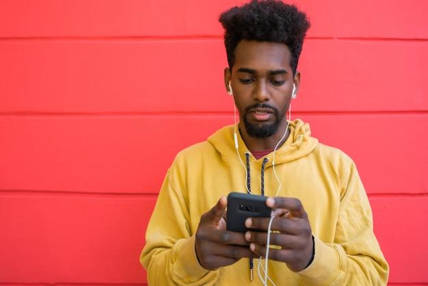 Afromens die zijn mobiele telefoon met behulp van.