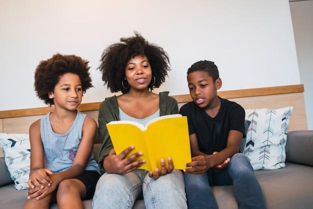 Afromoeder die een boek lezen aan haar kinderen.