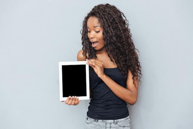 Afrovrouw die lege laptop computer over grijze muur toont