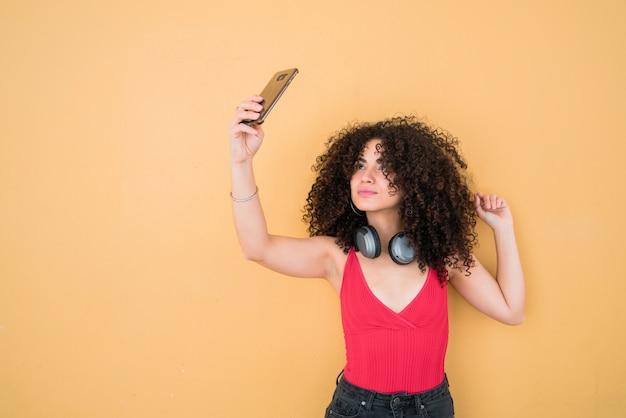 Afrovrouw die selfies met telefoon nemen.