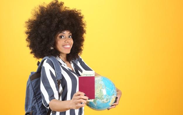 Afrovrouw met paspoort en aardebol, gele achtergrond