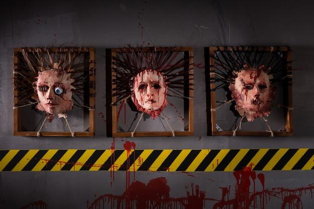 Afschuwelijke huiden van menselijke hoofden die in vierkante kaders boven het gele en zwarte waarschuwingssymbool zijn geplakt