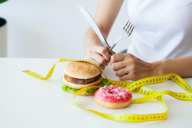 Afslanken concept, jonge vrouw met verzegelde mond junk food opgeven.