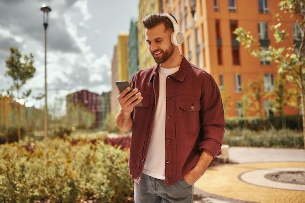 Afspeellijst instellingen gelukkige jonge man met stoppels in koptelefoon luisteren naar de muziek en houden