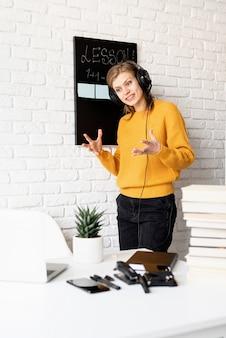 Afstand leren. e-leren. jonge lachende vrouw in gele trui en zwarte koptelefoon lesgeven online met behulp van videochat op laptop