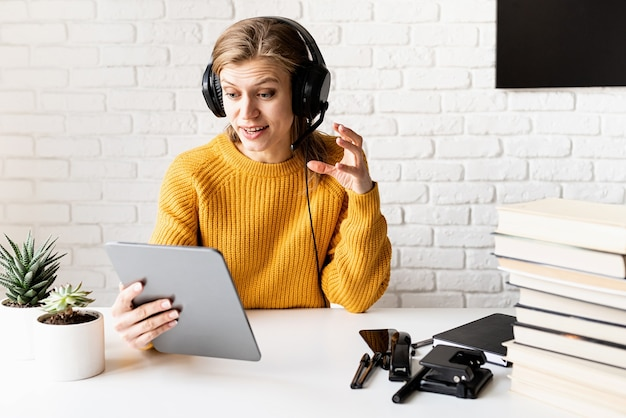 Afstand leren. e-leren. jonge lachende vrouw in gele trui en zwarte koptelefoon online studeren met behulp van digitale tablet