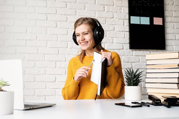 Afstand leren. e-leren. jonge lachende vrouw in gele trui en zwarte koptelefoon online studeren met behulp van laptop schrijven in notitieblok