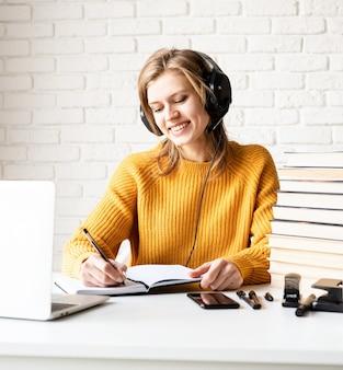 Afstand leren. e-leren. jonge lachende vrouw in zwarte koptelefoon online studeren met behulp van laptop schrijven in notitieblok