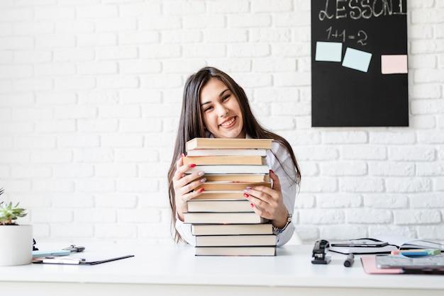 Afstand leren. e-leren. jonge leraar zitten met stapel boeken wegkijken klaar voor les