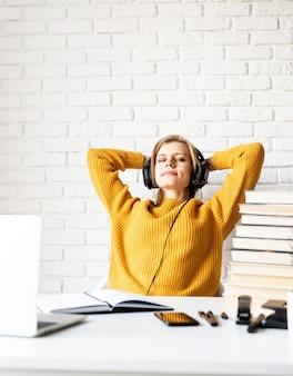 Afstand leren. e-leren. jonge vrouw in zwarte hoofdtelefoons die aan het bureau zitten dat na lange studie ontspant