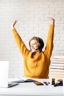 Afstand leren. e-leren. jonge vrouw in zwarte koptelefoon zit aan het bureau dat zich uitstrekt na lange studie