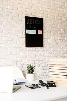 Afstand leren. e-leren. lichte en luchtige werkruimte, leraarstafel met laptop, boeken en briefpapier, focus op achtergrond