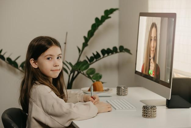 Afstand leren. een jong meisje met lang haar op afstand studeren van haar mannelijke leraar online. een mooi vrouwelijk kind leert thuis een les met een desktopcomputer. thuisonderwijs.