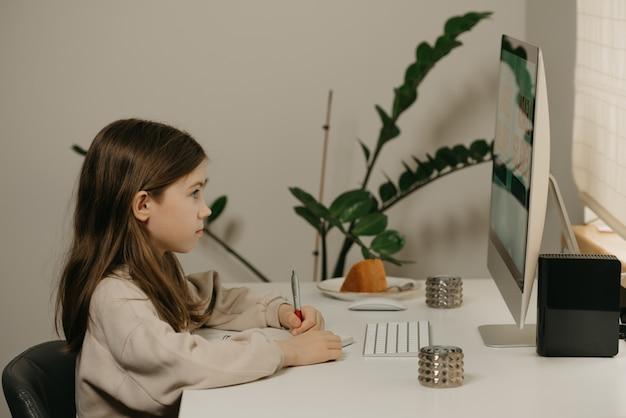 Afstand leren. een jong meisje met lang haar studeren op afstand online. een schattig vrouwelijk kind leert thuis een lesje met een alles-in-één computer. thuisonderwijs.