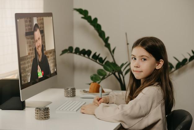 Afstand leren. een jong meisje met lang haar studeren op afstand van haar vrouwelijke leraar online. een mooi kind leert thuis een les met een desktopcomputer. thuisonderwijs.