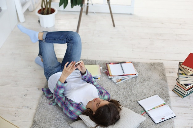 Afstand leren. jonge vrouwelijke student die thuis studeert, zich voorbereidt op universitaire examens, op de vloer ligt tegen een gezellig interieur, omringd met stapel boeken