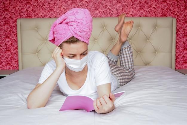 Afstand leren. thuisquarantaine. een jong kaukasisch meisje in een beschermend medisch masker en een handdoek op haar hoofd leest een boek op het bed. zelfstudie.