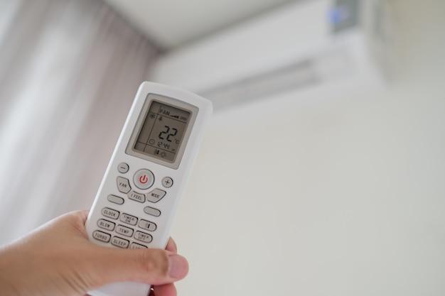 Afstandsbediening airconditioning bij de hand, sparen machtsconcept