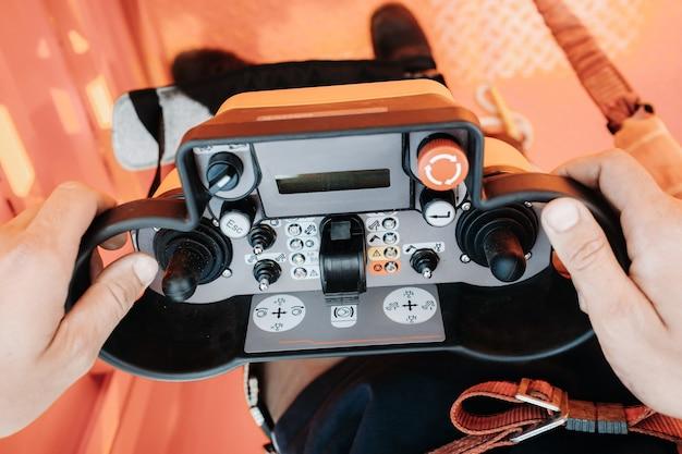 Afstandsbediening van een hijsautokraan in de handen van een persoon. paneel met joysticks en knoppen voor het bedienen van de telescopische bak van de kraan.