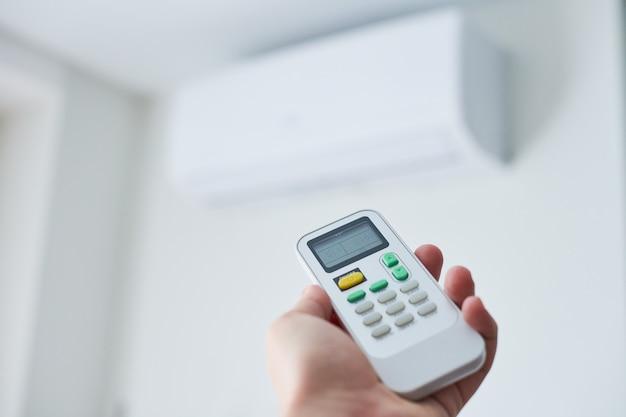 Afstandsbediening voor airconditioner in de hand. kamerconditie afstandsbediening
