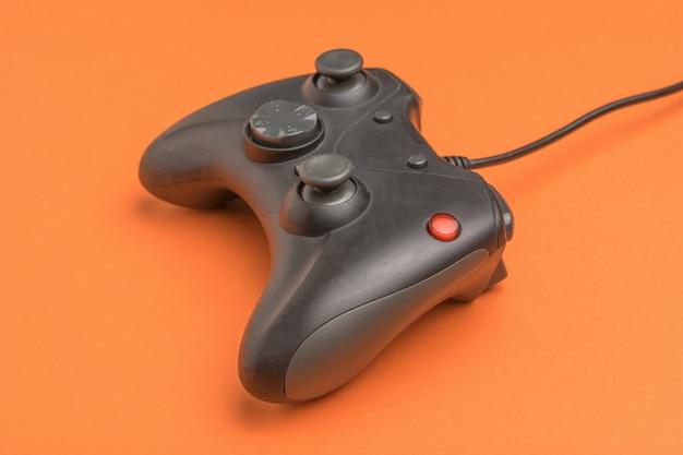 Afstandsbediening voor computerspelletjes op een oranje achtergrond. een apparaat voor het spelen van computerspelletjes.