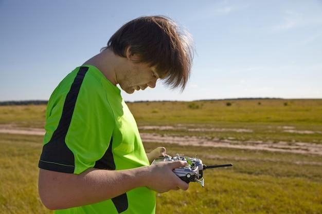 Afstandsbediening voor quadrocopter, close-up. zender voor het besturen van bewegend apparaat in mannelijke handen, onscherpe natuur achtergrond