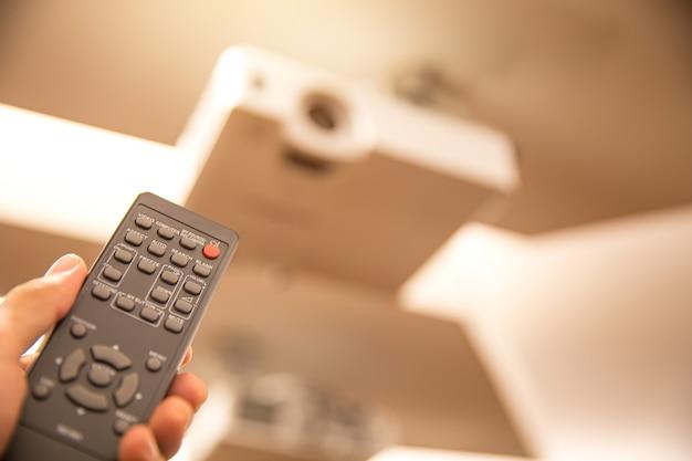 Afstandsbediening zet het plafond van de digitale projector in de bestuurskamer aan.