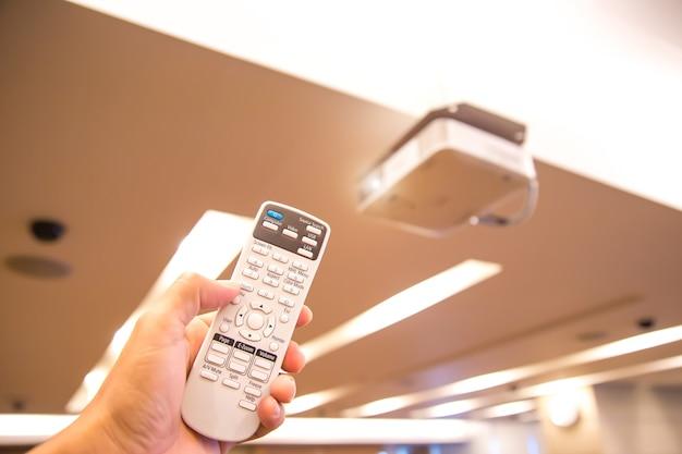 Afstandsbediening zet overheadprojector aan in directiekamer.