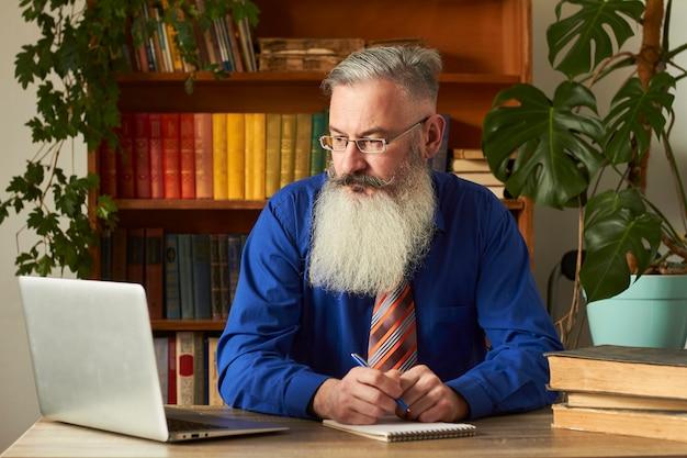 Afstandsonderwijs concept. docent professor tutor leert online discipline. de volwassen gebaarde mens beantwoordt de vraag van de leraar door laptop.