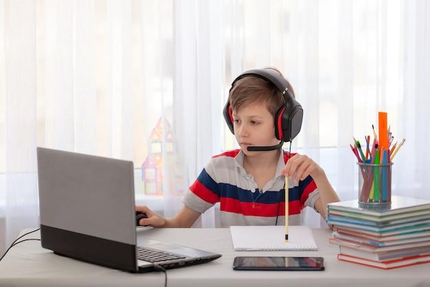 Afstandsonderwijs kind dat huiswerk schrijft met digitale tablet. concept online onderwijs.