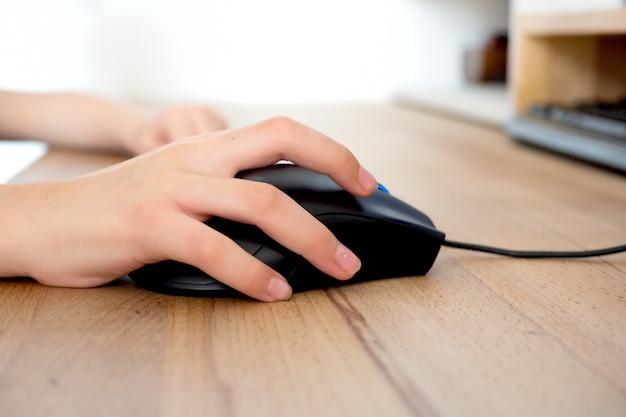 Afstandsonderwijs online onderwijs en werk. kind studeert op afstand vanuit huis op de bank. jongenshanden houden computermuis vast.