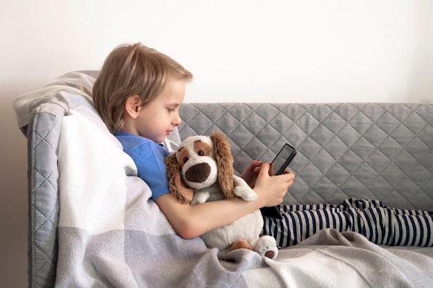 Afstandsonderwijs online onderwijs en werk. kind studeert op afstand vanuit huis op de bank. jongenshanden houden tablet vast.