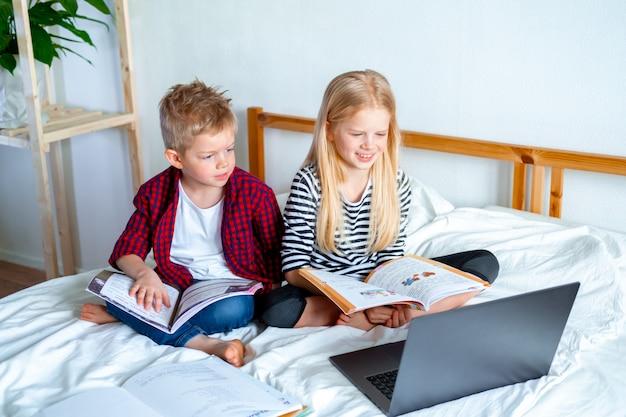 Afstandsonderwijs online onderwijs. schooljongen en meisje die thuis met digitaal tabletlaptop notitieboekje bestuderen en schoolthuiswerk doen. zittend op bed met trainingsboeken.