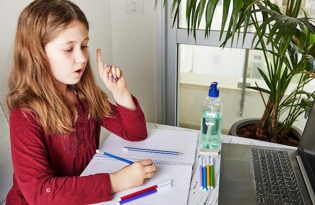 Afstandsonderwijs online onderwijs. schoolmeisje dat thuis met laptop bestudeert en schoolthuiswerk doet. trainingsboeken en gekleurde viltstiften op tafel, gel met 70 procent alcohol