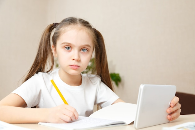 Afstandsonderwijs online onderwijs. schoolmeisje huiswerk op tablet thuis. quarantaine
