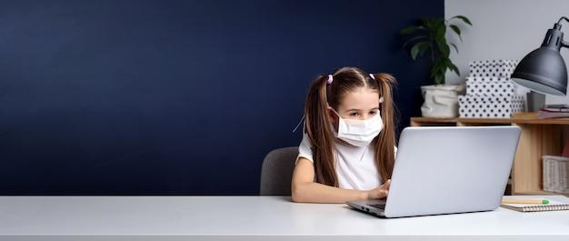 Afstandsonderwijs online onderwijs. schoolmeisje in medisch masker dat thuis bestudeert, bij laptop notitieboekje werkt en schoolhuiswerk doet. coronavirus quarantaine.
