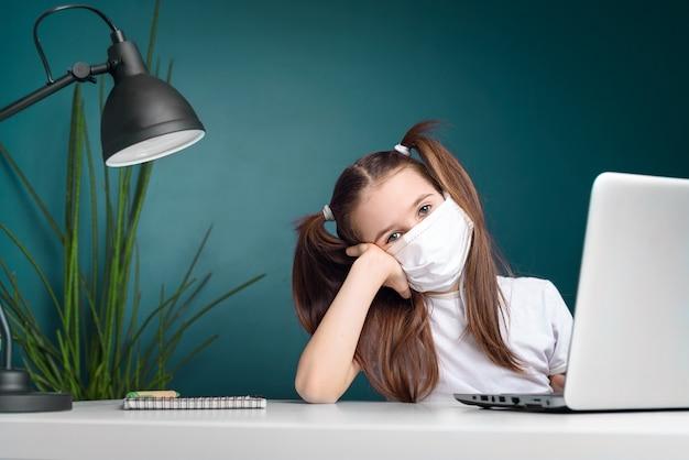 Afstandsonderwijs online onderwijs. schoolmeisje in medisch masker dat thuis bestudeert, bij laptop notitieboekje werkt en schoolhuiswerk doet. coronavirus quarantaineconcept