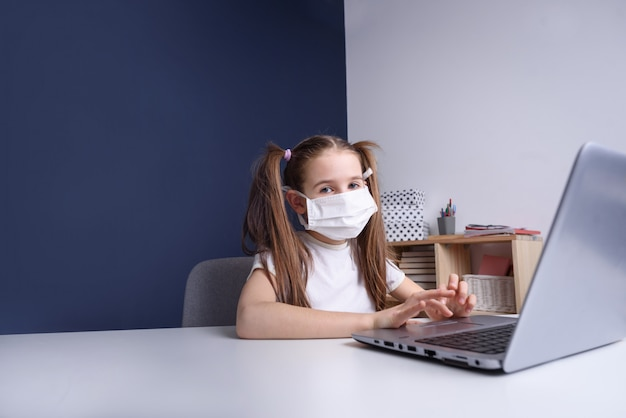 Afstandsonderwijs online onderwijs. schoolmeisje in medisch masker dat thuis bestudeert, bij laptop notitieboekje werkt en schoolhuiswerk doet. covid quarantaine concept