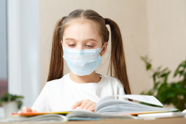 Afstandsonderwijs online onderwijs. schoolmeisje in medisch masker doet huiswerk o thuis. quarantaine