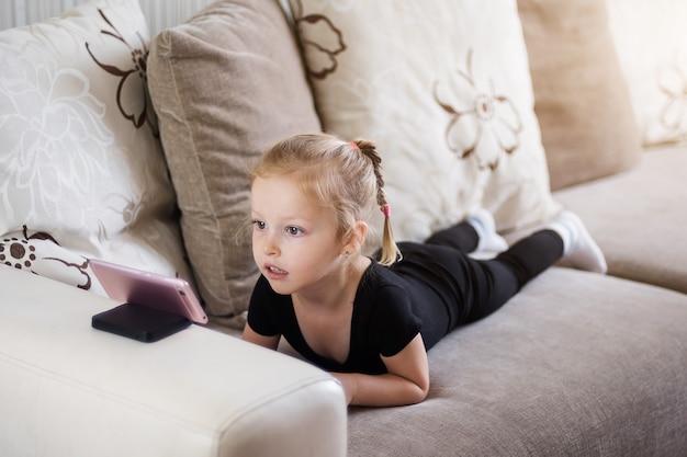 Afstandsonderwijs, online onderwijs voor kinderen. klein meisje studeren thuis voor de smartphone. kind kijken naar online tekenfilms, computerverslaving voor kinderen, ouderlijk toezicht.