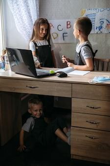 Afstandsonderwijs thuisonderwijs lessen op afstand concept twee schoolkinderen in de buurt van opengeklapte laptop en