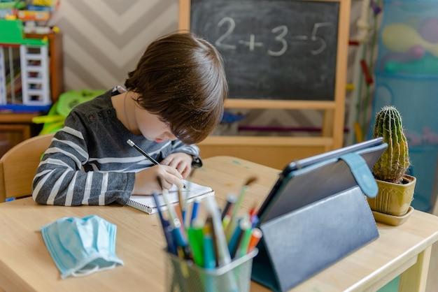 Afstandsonderwijs voor kinderen tijdens de coronavirusepidemie. een jongen zit aan een tafel en voert taken uit van een leraar op internet.
