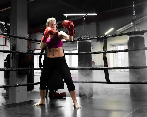 Afstandsschot atletische vrouw training voor een bokswedstrijd