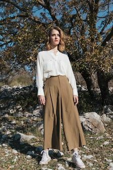 Afstandsschot staande vrouw met casual outfit