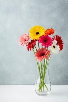 Afstandsschot van een minimalistische vaas met gerberabloemen