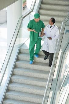Afstandsschot van twee artsen die de trap van het ziekenhuis aflopen